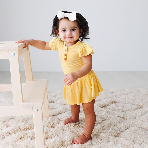 Baby standing wearing Banana Cream Ruffled Cap Sleeve Henley Twirl Skirt Bodysuit