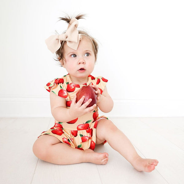 Baby holding an apple wearing Finn Ruffled Cap Sleeve Henley Twirl Skirt Bodysuit