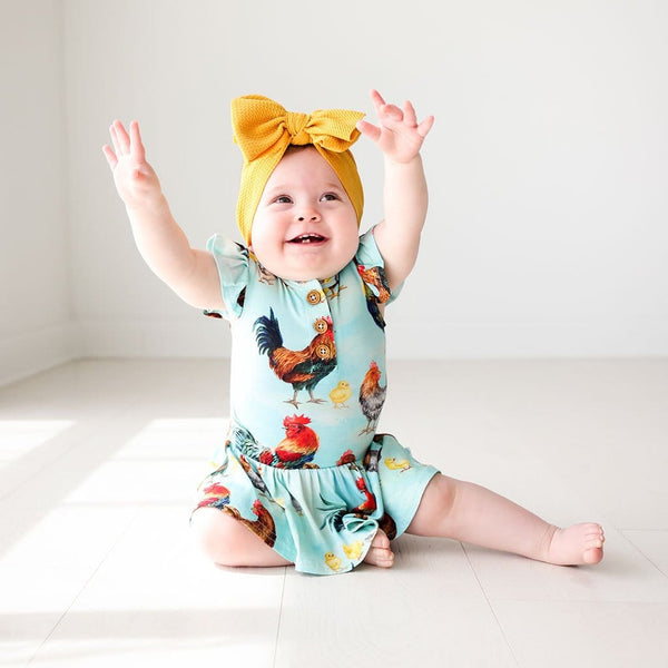 Baby in yellow ribbon wearing Rhett Ruffled Cap Sleeve Henley Twirl Skirt Bodysuit