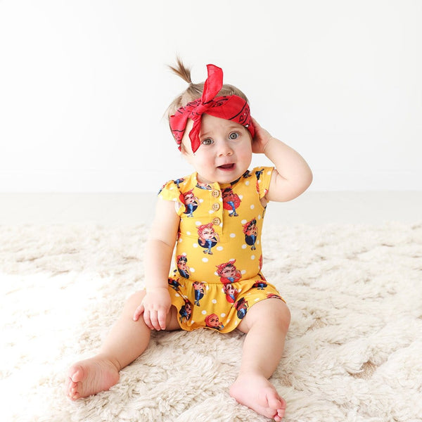 Baby sitting wearing Rosie the Riveters Ruffled Cap Sleeve Henley Twirl Skirt Bodysuit