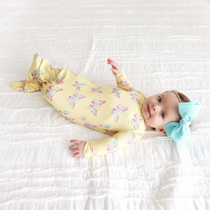 Baby lying in bed wearing Keira Zippered Gown