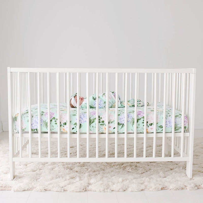 Baby lying on white crib with Erin Crib Sheet