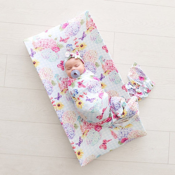 Baby lying on bed with Nicolette Pad Cover