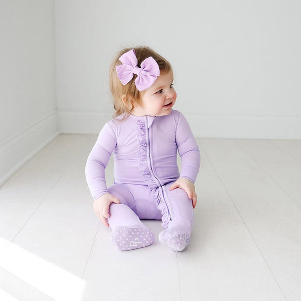 Sitting baby wearing Amethyst Footie Ruffled Zippered One Piece