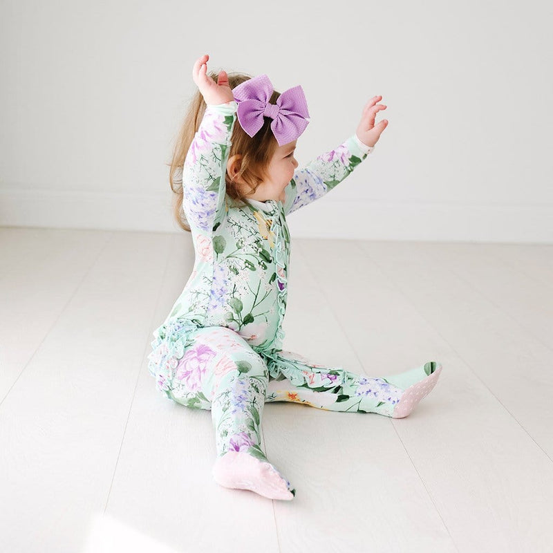 Baby playing wearing Erin Footie Ruffled Zippered One Piece