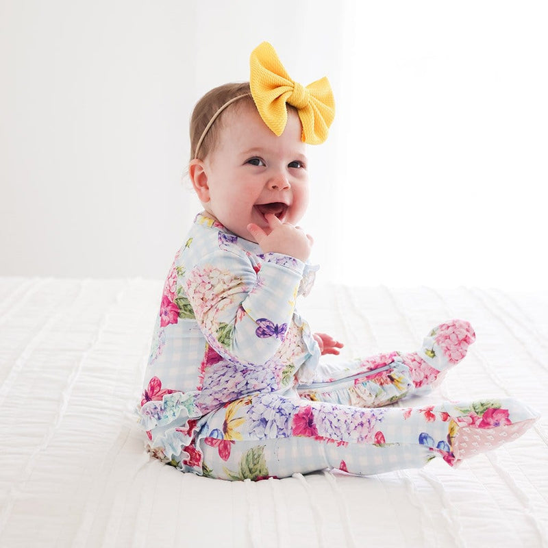 Baby on bed wearing Nicolette Footie Ruffled Zippered One Piece