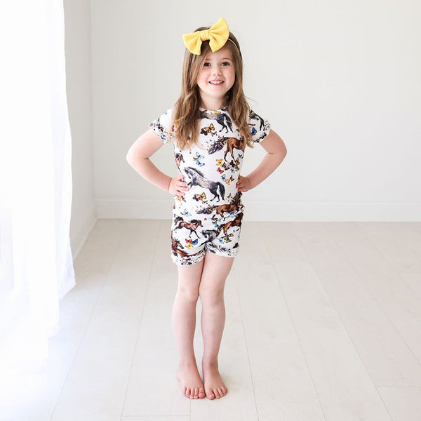 Baby in yellow ribbon wearing animal printed Claire Ruffled Short Sleeve Ruffled Short Pajamas