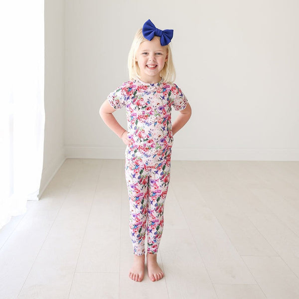 Toddler in blue ribbon wearing Vivienne Ruffled Short Sleeve Pajamas