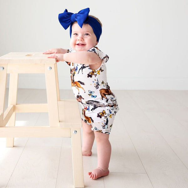 Baby in blue ribbon wearing Claire Ruffled Cap Sleeve Henley Short Romper