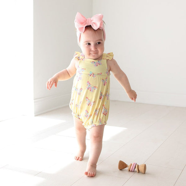Baby wearing Keira Ruffled Cap Sleeve Bubble Romper