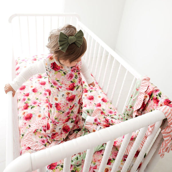 Baby in crib wearing Marlene Sleeveless Ruffled Sleep Bag 0.5 Tog with matching floral print