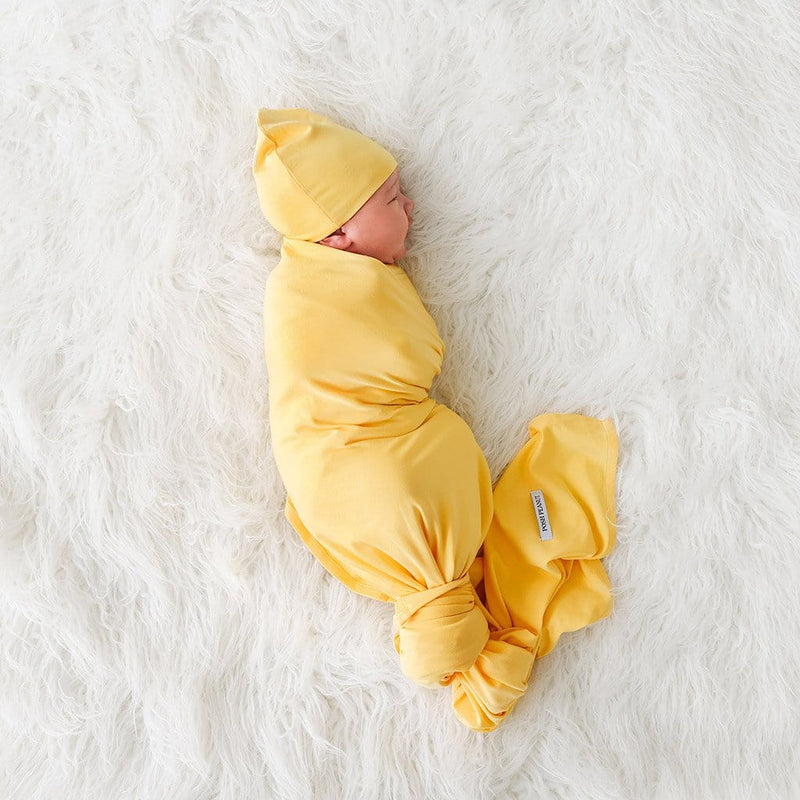 Baby wearing Banana Cream Swaddle Beanie Set