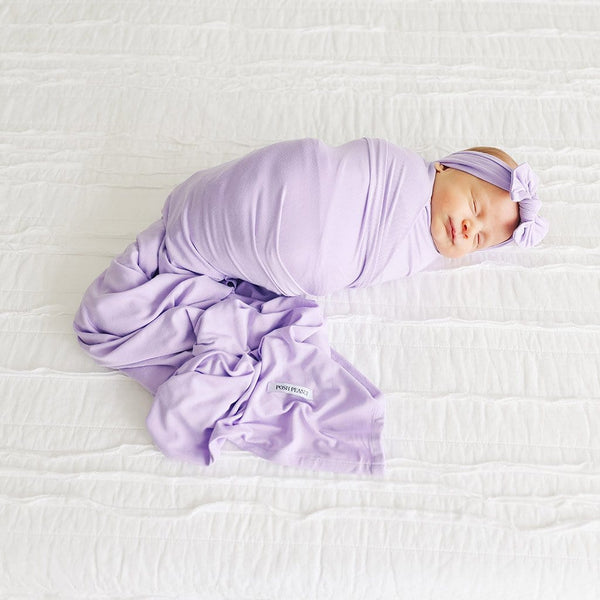 Baby on bed wearing Amethyst Swaddle Headband Set