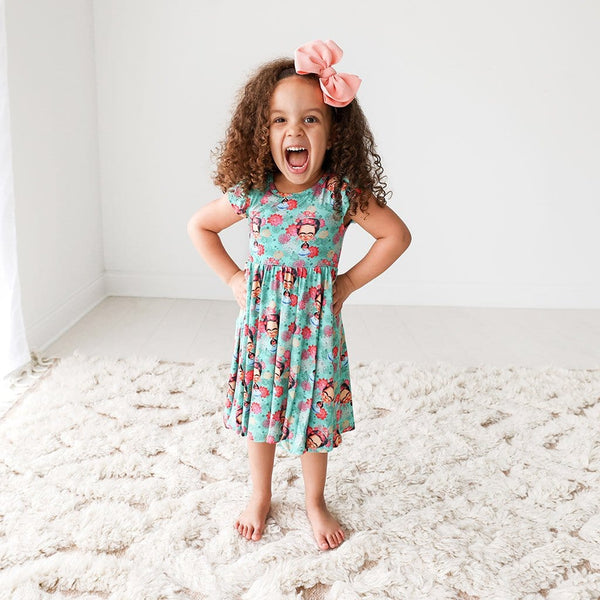 Toddler wearing Frida Kahlo Ruffled Cap Sleeve Twirl Dress