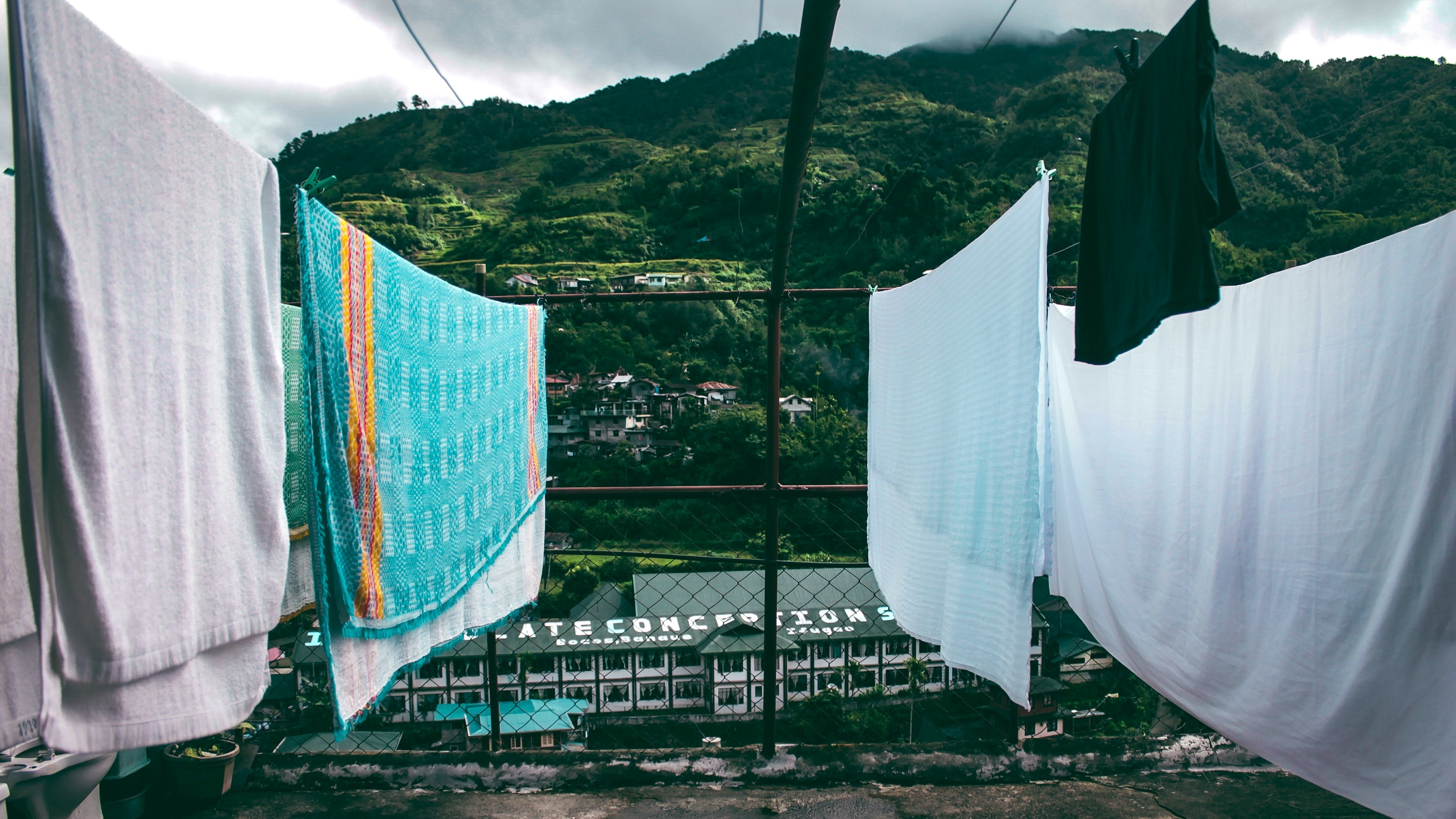 Forested mountains against the background of a stormy sky. Towels hang to dry in the foreground on a rooftop.