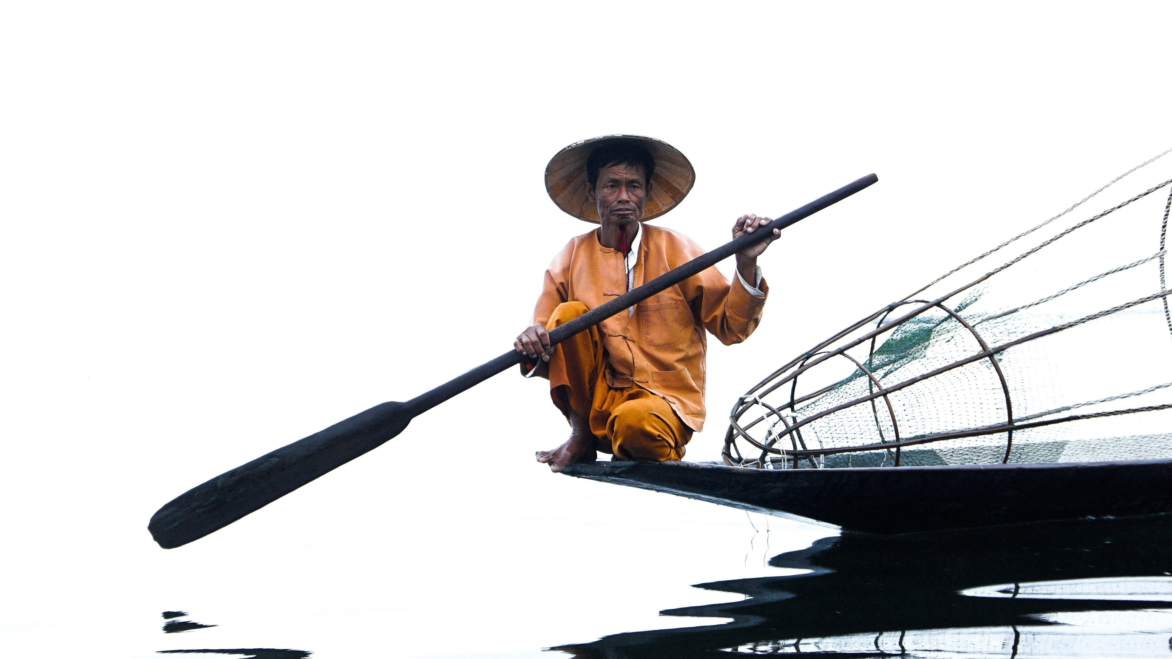 Burmese fisherman in yellow paddling boat over smooth waters