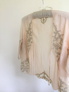 Our latest lovely vintage lingerie discovery, a peach 1940s jacquard woven silk bed jacket with drawn lace work and silk georgette and tulle embellishment appliqué.