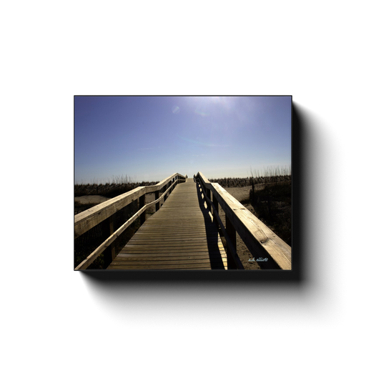 A photograph of a Tybee beach Georgia boardwalk facing the ocean. Taken by the photographer a.d. elliott #TakethebackRoads.  Available in print sizes 8x10 to 24x30 and printed on high quality, artist-grade stock and folded around a lightweight frame to give them a gorgeous, gallery-ready appearance.