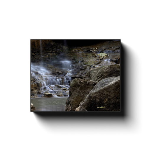 A long exposure photograph of a cascade on Pinion Creek in Bella Vista Arkansas. Taken by the photographer a.d. elliott - Take the Back Roads #TaketheBackRoads  Printed on high quality, artist grade stock and folded around a lightweight frame to give them a gorgeous, gallery ready appearance. With acid free ink that will last without fading or chipping, Features a scratch-resistant UV coating. Wipes clean easily with a damp cloth or to remove dust, vacuum gently using a soft brush attachment.