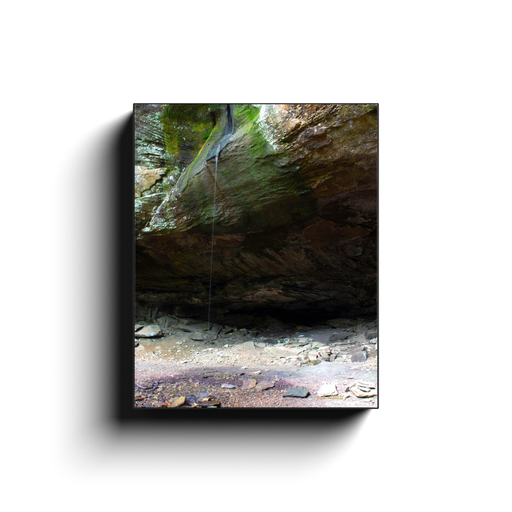 A long exposure photograph of a trickle of water over a bluff, taken at Pam's Grotto Arkansas by the photographer a.d. elliott  Printed on high quality, artist grade stock and folded around a lightweight frame to give them a gorgeous, gallery ready appearance. With acid free ink that will last without fading or chipping, Features a scratch-resistant UV coating. Wipes clean easily with a damp cloth or to remove dust, vacuum gently using a soft brush attachment.