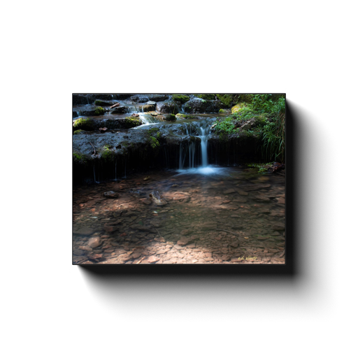 A long exposure photograph of a small cascade on Parks Spring in Bentonville Arkansas. Taken by the photographer a.d. elliott.  Printed on high quality, artist-grade stock and folded around a lightweight frame to give them a gorgeous, gallery-ready appearance. With acid-free ink that will last without fading or chipping, Features a scratch-resistant UV coating. Wipes clean easily with a damp cloth or to remove dust, vacuum gently using a soft brush attachment.
