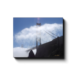 A photograph of San Francisco's Golden Gate Bridge behind clouds. Taken by the Arkansas photographer a.d. elliott #TaketheBackRoads  Printed on high quality, artist-grade stock and folded around a lightweight frame to give them a gorgeous, gallery-ready appearance. With acid-free ink that will last without fading or chipping, Features a scratch-resistant UV coating. Wipes clean easily with a damp cloth or to remove dust, vacuum gently using a soft brush attachment.