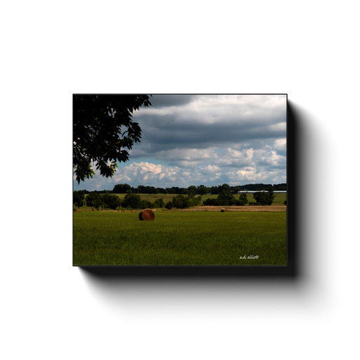 Landscape photography of hay bales in a field. Taken by the photographer a.d. elliott.  Printed on high quality, artist-grade stock and folded around a lightweight frame to give them a gorgeous, gallery-ready appearance. With acid-free ink that will last without fading or chipping, Features a scratch-resistant UV coating. Wipes clean easily with a damp cloth or to remove dust, vacuum gently using a soft brush attachment.