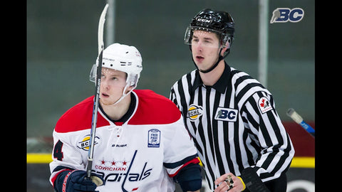 Linesman Brett Mackey skates behind a Cowichan Capitals hockey player