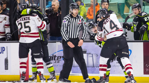 Linesman Chad Huseby looks on as two WHL hockey players fight