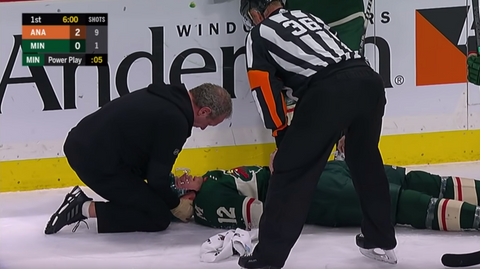 NHL referee Dean Morton looks on as Eric Staal lays injured on the ice during NHL game