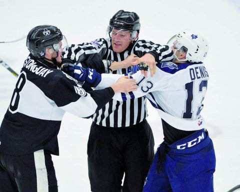 Linesman Maxime Chaput breaks up a fight between two hockey players in the QMJHL
