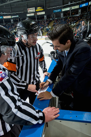 Referee Mike Langin talks to a coach during a WHL hockey game