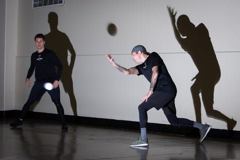 Two hockey referees playing wall ball before a game