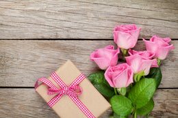 Image of pink roses and a gift wrapped in brown paper with gingham red and white ribbon, all on top of a wooden plank