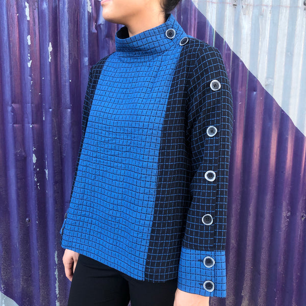 A classic check with stripes and large buttons are featured in this shorter royal blue and black tunic top. Pair this cozy piece with denim or black pants for an easy outfit. Other features include: a comfortable feel, thicker but soft texture, and full length sleeve. This piece is a classic that will never go out of style.