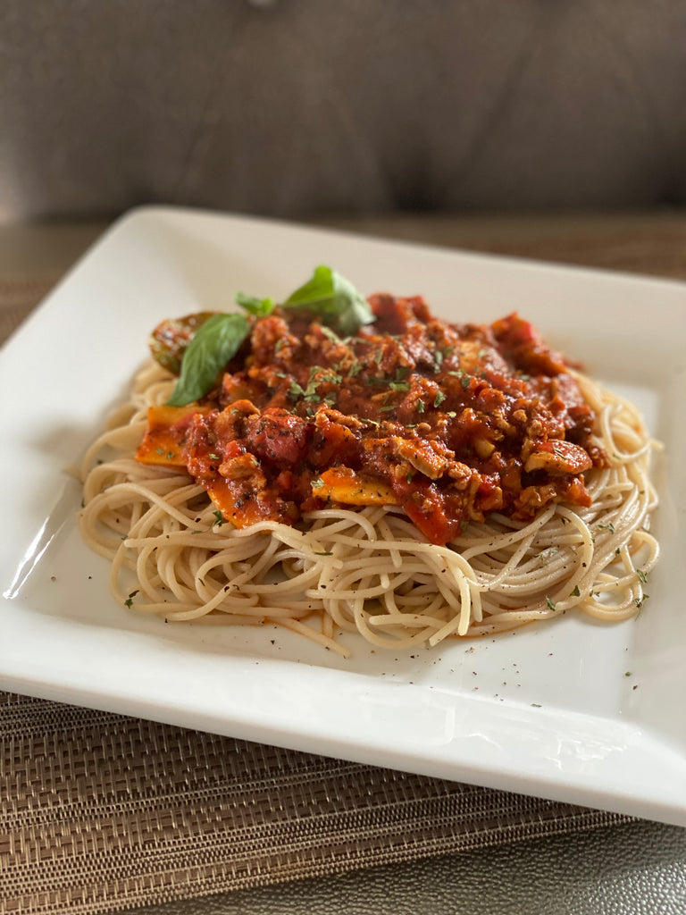 Turkey, mushroom, and tomato meat sauce served over a plate of spaghetti noodles and garnished with black pepper, parsley, and basil.