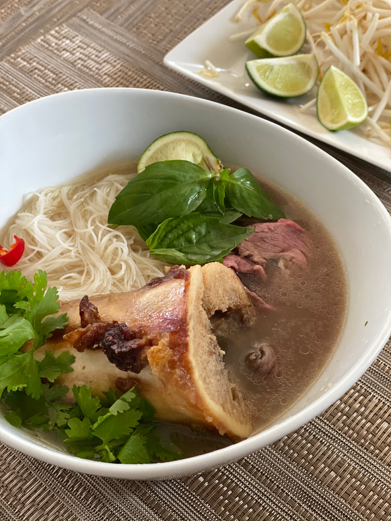 Authentic Vietnamese beef noodle Pho Soup, garnished with basil, cilantro, hot peppers, and lime.