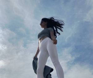 Elaine Huba, Master Personal Trainer, standing in-front of a cloudy sky with her hair and jacket blowing in the wind.