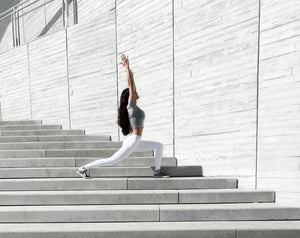 Elaine Huba, Master Personal Trainer, demonstrating a yoga pose on the stairs of Calgary's central library.