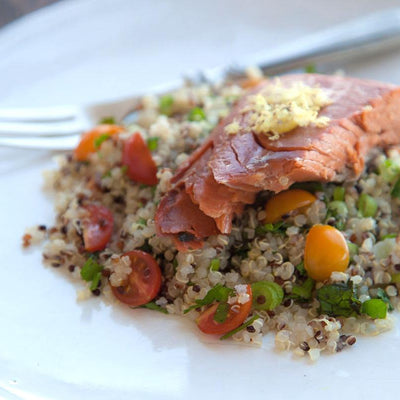 A plate of quinoa with cherry tomatoes, green onions, and a pice of salmon on top