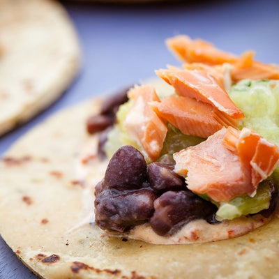 Chipotle Sour Cream, black beans, salmon layered on a small tortilla
