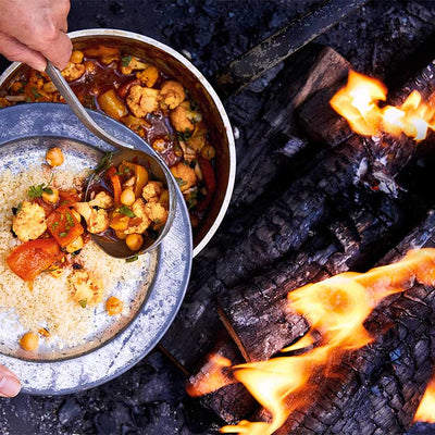 Person scooping cauliflower from a pan over a campfire onto a plate of couscous