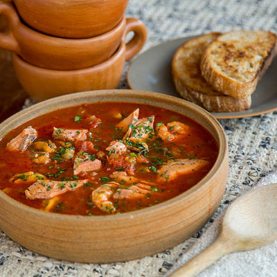 A tomato-rich stew with chunks of salmon in a wooden bowl with pieces of toasted bread on the side