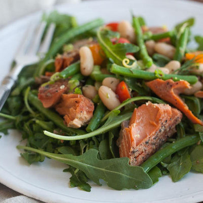Salmon and four bean salad on a white plate