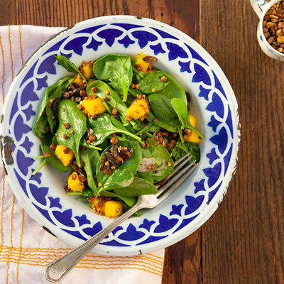Baby spinach salad with diced mango and sprinkled with lime savory seeds in a pretty blue and white patterned bowl