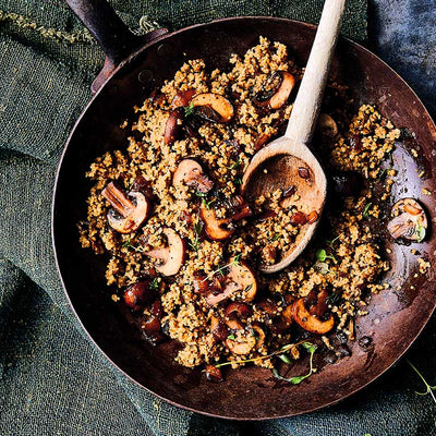 Skillet with mushroom savory grains, thyme, onions, and crispy mushrooms, with wooden spoon