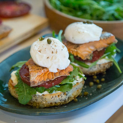 A sliced seed bagel side-by-side on a blue plate topped with greens, large tomato slice, a piece of salmon, and poached egg