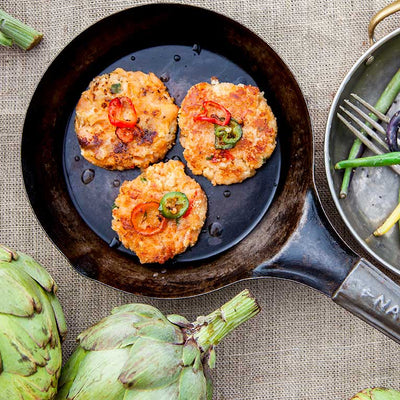 A cast iron pan with three salmon cakes topped with fresh herbs with artichokes, beans, and gourds on the table