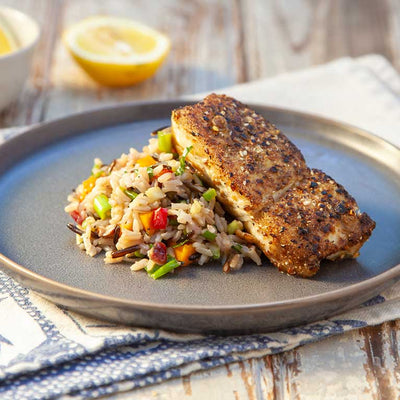 A thick piece of white fish coated with mellow curry savory seeds, plated with colorful savory grains and vegetables