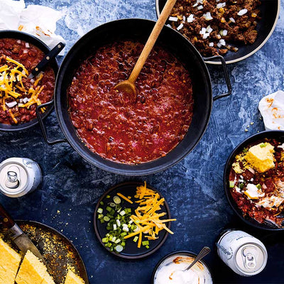 A pot and bowls of spicy red bean chili with toppings and cans of Long Root Wit beer